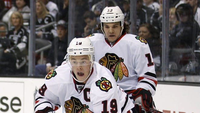 Daniel Carcillo, back, was playing on a line with Jonathan Toews, front, on Saturday before he was injured.
