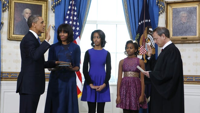 President Obama takes the oath of office from U.S. Supreme Court Chief Justice John Roberts as first lady Michelle Obama holds the bible and daughters Malia and Sasha look on.