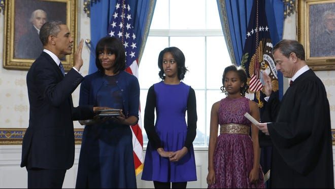 President Obama takes oath of office as first lady Michelle Obama and daughters Malia  and Sasha look on.