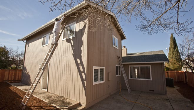 Workers put the finishing touches on a home in Suisun, Calif.,  on Jan 19. It is owned by  Waypoint Homes, which purchased this home as an investment property to rent.