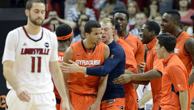 Syracuse Orange guard Michael Carter-Williams (1) celebrates with his teammates after time expired in the second half against the Louisville Cardinals on Saturday.  Syracuse defeated Louisville 70-68.