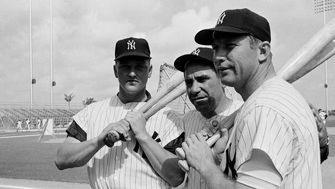 Yogi Berra is flanked by Roger Maris, left, and Mickey Mantle on the first day of spring training in 1964, a season that ended with a seven-game World Series loss and Berra's firing as manager.