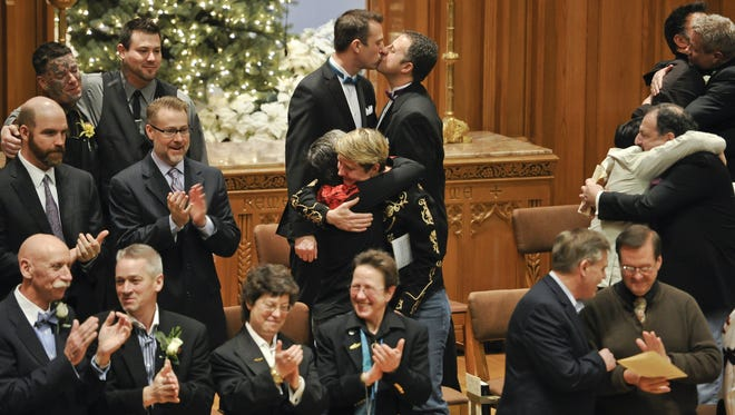 Leif Anderson and Alix Mendonco kiss at a wedding ceremony for 25 same-sex couples in Seattle.
