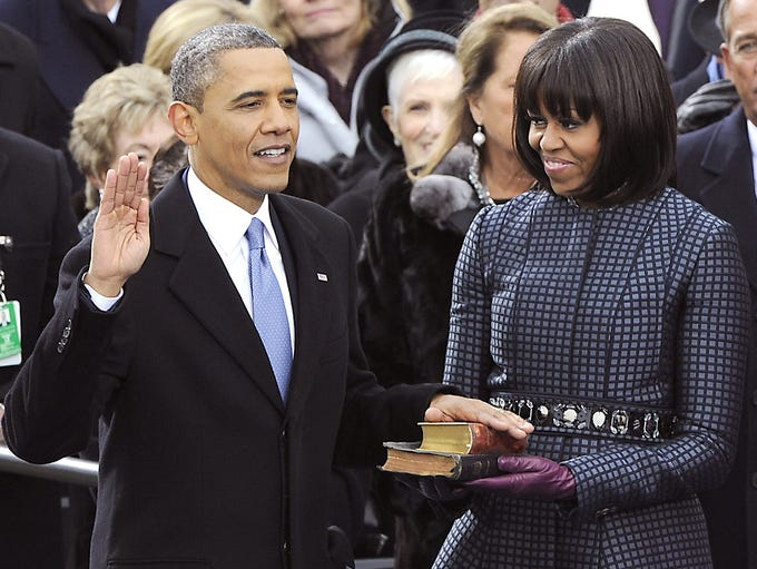 President Obama takes the oath of office from Supreme Court Chief Justice John Roberts as his wife, first lady Michelle Obama, holds two Bibles at the Capitol in Washington.