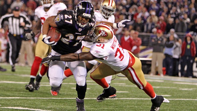Baltimore Ravens running back Ray Rice is tackled by San Francisco 49ers safety Donte Whitner during the team's game in the 2011 regular season.