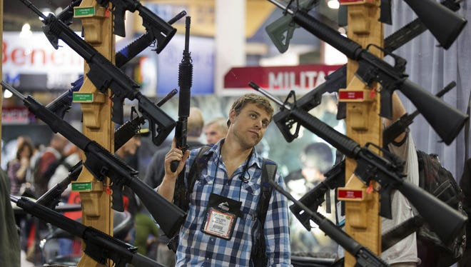 Michael Kiefer, of DeFuniak Springs, Fla., checks out a display of rifles at the Rock River Arms booth during the 35th annual SHOT Show, Thursday, Jan. 17, 2013, in Las Vegas.