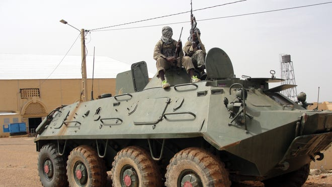 Fighters of the Movement for Oneness and Jihad in West Africa (MUJAO), an al-Qaeda offshoot, stand guard on a tank abandoned by the Malian Army near Gao airport on Aug. 7.