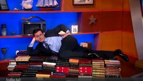 Stephen Colbert lounges on a stack of Bibles on Monday's 'Colbert Report.'