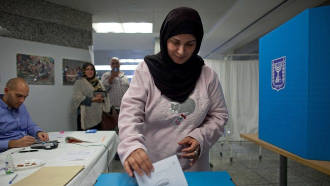 An Israeli Arab woman casts her vote during the Israeli General Election on Tuesday in Tel Aviv.