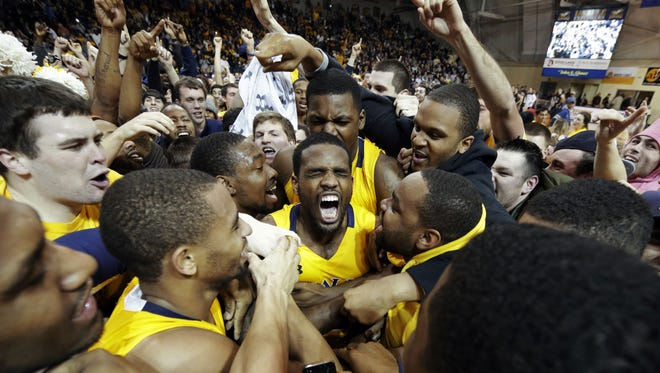 La Salle's Ramon Galloway, center, is mobbed by teammates and fans after La Salle upset Butler in Philadelphia.