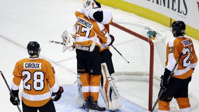Philadelphia Flyers' Wayne Simmonds (17) celebrates with Ilya Bryzgalov, as Claude Giroux (28) and Luke Schenn look on after their 2-1 win over the New York Rangers Thursday, Jan. 24, 2013, in Philadelphia.