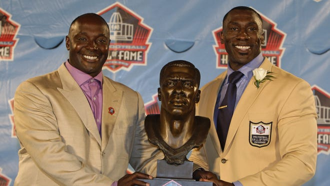 Shannon Sharpe, right, poses with a bust of himself  as presenter and brother Sterling stands next to him during the induction ceremony at the Pro Football Hall of Fame on Aug. 6, 2011, in Canton, Ohio.