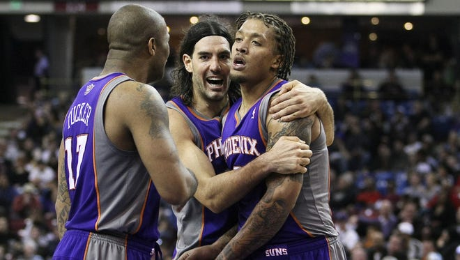 The Suns' P.J. Tucker, left, Luis Scola, center and Michael Beasley celebrate after a three-point basket during the fourth quarter.