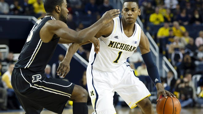 Michigan Wolverines forward Glenn Robinson III is defended by Purdue Boilermakers guard Rapheal Davis in the first half at Crisler Center.