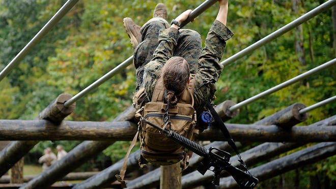 A female Marine pulls herself through an obstacle course during the combat endurance test on Aug. 28 in Quantico, Va. This is the first event in the Marine Infantry Officer Course.