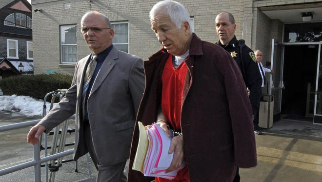 Former Penn State University assistant football coach Jerry Sandusky, center, leaves the Centre County Courthouse escorted by Centre County Sheriff Denny Nau, left, after attending a post-sentence motion hearing in Bellefonte, Pa.