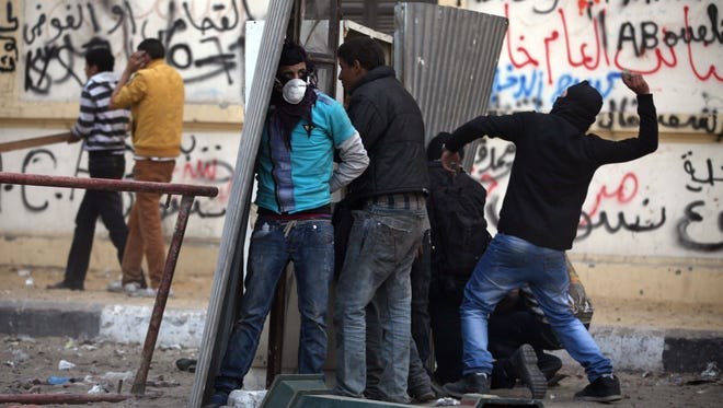Egyptian protesters take cover as they clash with riot police, not seen, near Tahrir Square, Cairo, Egypt, Friday, Jan. 25, 2013.