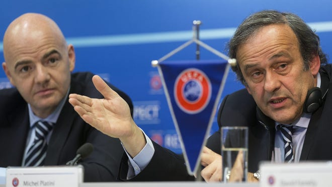 UEFA President Michel Platini, right, sitting next to UEFA General Secretary Gianni Infantino, left, answers to media during a press conference after the UEFA Executive Committee Meeting.