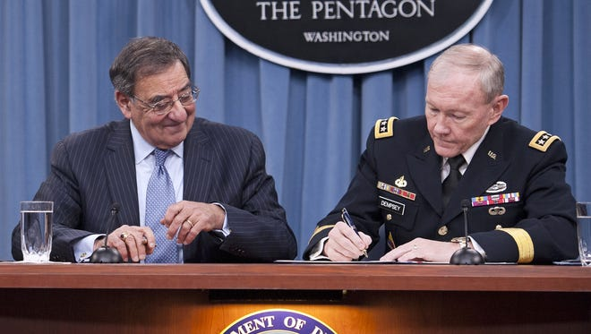 Defense Secretary Leon Panetta watches Joint Chiefs Chairman Gen. Martin Dempsey sign a memorandum ending the 1994 ban on women serving in combat roles in the military on Thursday at the Pentagon.