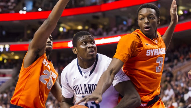 Villanova Wildcats forward Mouphtaou Yarou (13) is defended by Syracuse Orange forwards Jerami Grant (3) and Rakeem Christmas (25) during the first half of Saturday's game.