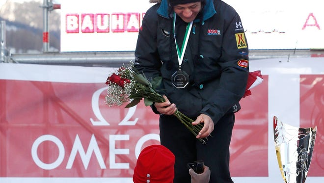 Nick Taylor, left, a brakeman from the USA  bob team, proposes to Elana Meyers, new bobsled silver medalist, during the medal ceremony of the two-woman Bobsled World Championship competition in St. Moritz, Switzerland.