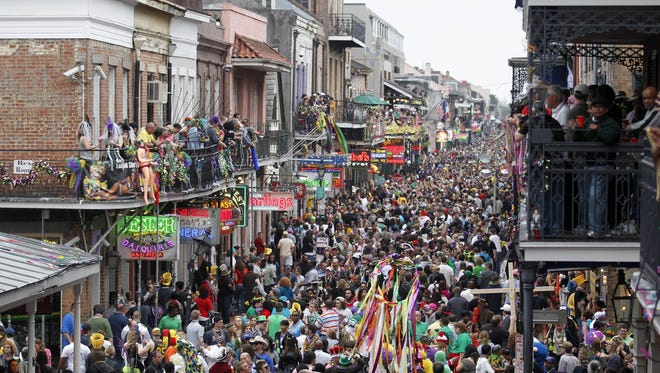 Crowds throng Bourbon Street in the French Quarter on Mardi Gras day in New Orleans in 2011. This year it comes on the heels of the Super Bowl.