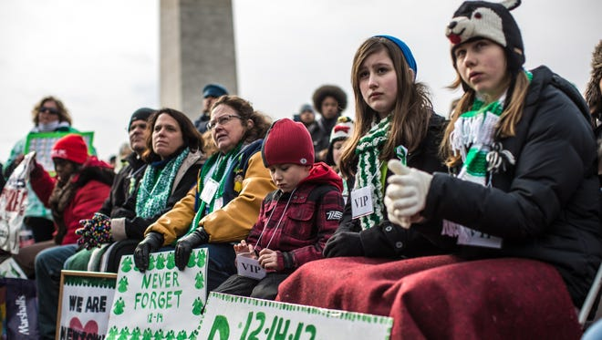 Advocates of stricter gun control laws -- including Sophie Ackert, second from right, and Maya Neuhoff, right, both 13 and from Newtown, Conn. --  gather on the National Mall Saturday for a rally following a march through downtown Washington.