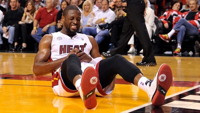 Heat guard Dwyane Wade clutches his finger after landing on the ground during Friday's 110-88 win vs. the Pistons.