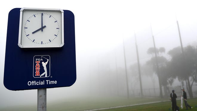 Players try to warm up on the range, but they aren't starting Round 3 at Torrey Pines until the fog lifts.