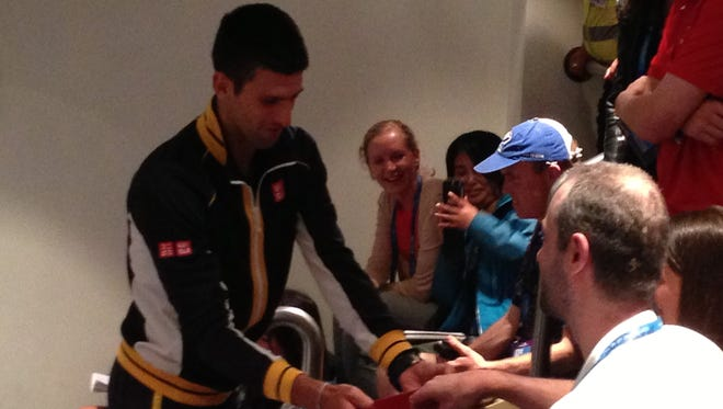 Novak Djokovic hands out chocolates to reporters at his post-match news conference.