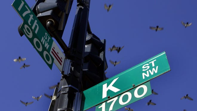 Pigeons fly over the intersection of 17th and K streets in northwest Washington Thursday, Jan. 26, 2006.  K Street has long been invoked as shorthand for moneyed lobbyists who ply influence in the city.