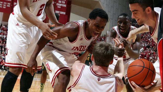 From left, Indiana teammates Christian Watford, Yogi Ferrell and Will Sheehey congratulate Cody Zeller for taking a charge with 14.3 seconds to play that helped seal the Hoosiers' victory against Michigan State.