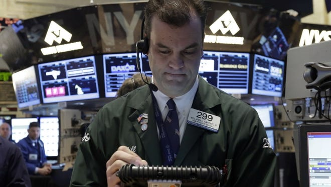Trader William Lawrence works on the floor of the New York Stock Exchange, Friday, Jan. 25, 2013. (AP Photo/Richard Drew)
