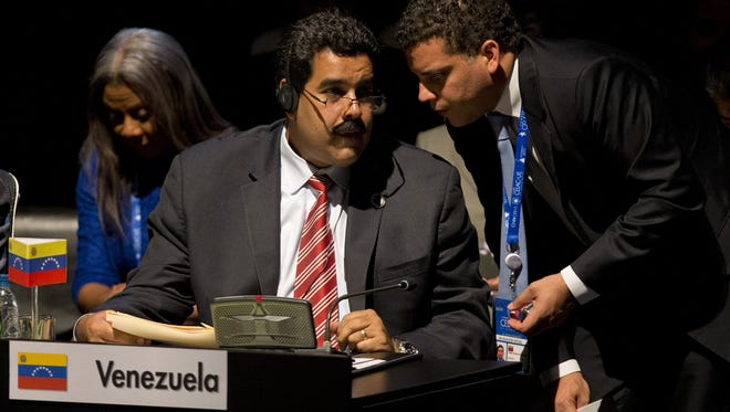 An aide has the ear of Venezuelan Vice President Nicolas Maduro during the closing ceremony of a 60-nation summit among leaders from the European Union, Latin America and the Caribbean in Santiago, Chile, on Sunday.