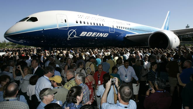 In this file photo from July 8, 2007, visitors  look at and take photos of the first production model of the new Boeing 787 airplane after it was unveiled to an audience of several thousand at Boeing's assembly plant in Everett, Wash.