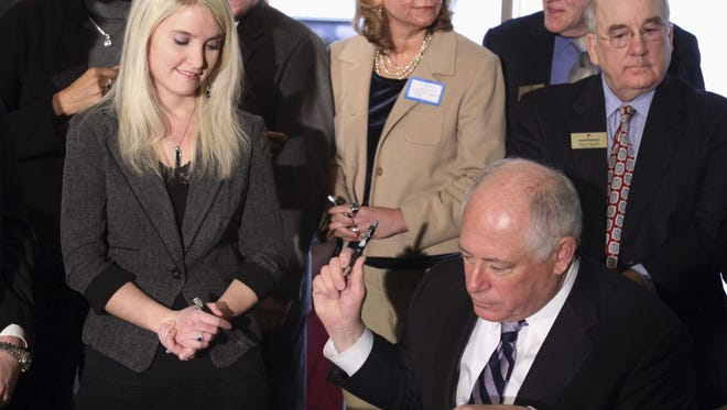 Erin Merryn of Schaumburg, Ill., looks down at Illinois Gov. Pat Quinn as he signs a bill Thursday called Erin's Law. The law requires all Illinois public schools to have sexual assault and abuse prevention and awareness programs.