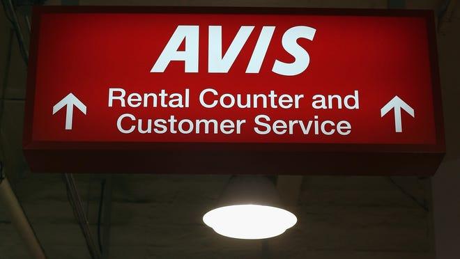 Signs hang in an Avis rental car branch in New York City.