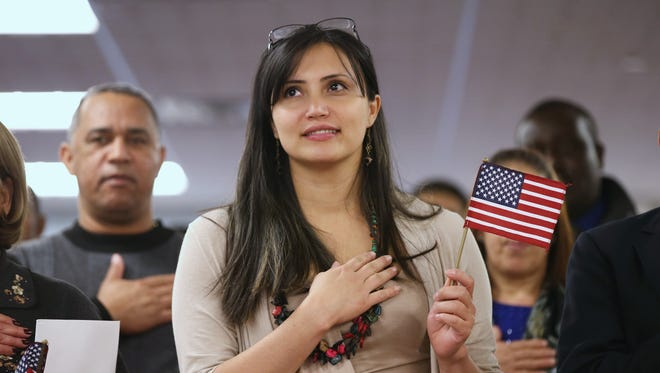 Immigrants listen to the National Anthem Monday during a naturalization ceremony at a U.S. Citizenship and Immigration Services office in Newark.