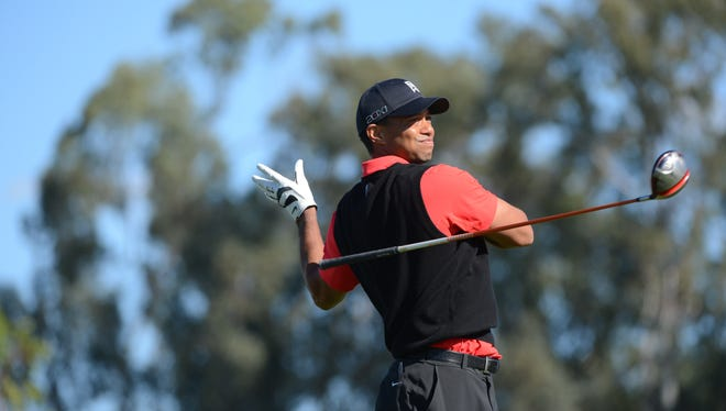 Tiger Woods lets loose of his driver after an errant tee shot Monday during the final round of the Farmers Insurance Open. Woods wasn't at his best, but he had a big lead.