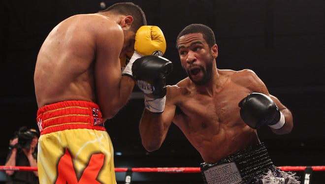 Lamont Peterson, right, defeated Amir Khan for the WBA and IBF 140-pound titles. Monday, Peterson signed with Golden Boy.