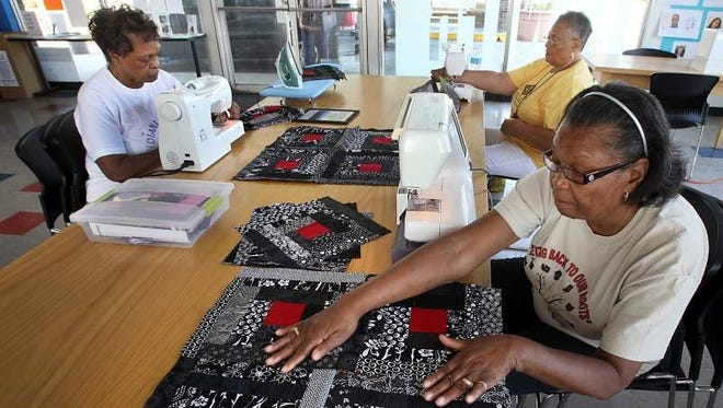 Annette Smith, left, Betty Frierson and Ruth Edwards, members of the Indy Connection Quilters, work on the next quilt for the Lynch Quilt Project titled Red Rum Summer.