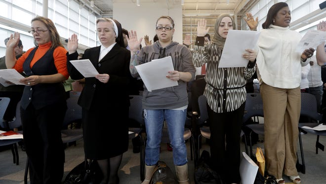Immigrants take the U.S. oath of citizenship Monday in Irving, Texas.