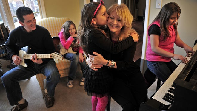 Natasha Clark, 9, kisses her mother, Kim Clark, as Alan Clark, left, and Nastia, 11, second from left, look on at their home in Franklin, Tenn., on Jan. 25, 2013. At right is Kristina, 13, playing the piano. The Clarks adopted their daughters from Russia.