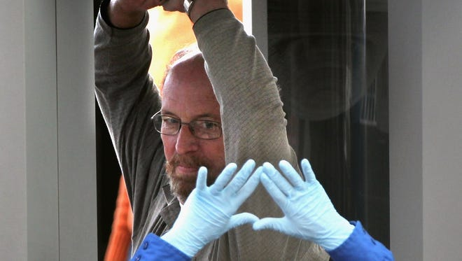 A TSA agent instructs a flier during a full-body scan at a Denver airport.