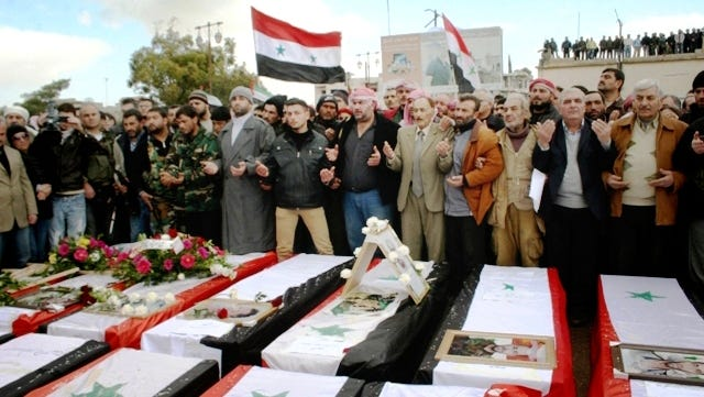 In this Jan. 23 photo released by the Syrian official news agency, SANA, Syrians take part in a funeral procession for those killed in a car bomb explosion at the headquarters of a pro-government militia late Monday in the central town of Salamiya, Syria.