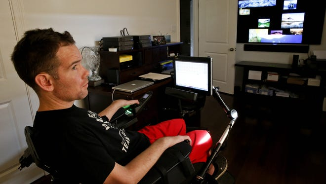 "Former New Orleans Saints player Steve Gleason, who was diagnosed with ALS in January 2011, is shown in his in-home ""lab,"" demonstrating eye-tracking technology that allows him to write, talk with a synthetic voice, open doors and run electronics in his home near Lake Pontchartrain."