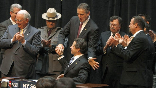 New York Gov. Andrew Cuomo, seated at center, shakes hands with Lt. Gov. Robert Duffy after signing the NY Safe Act in Rochester, N.Y., on  Jan. 16.