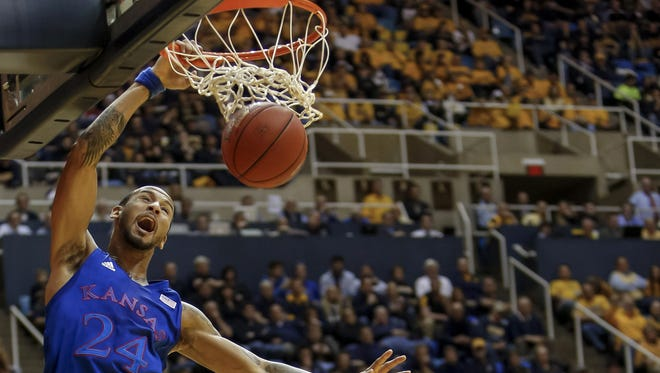 Kansas' Travis Releford dunks over West Virginia's Jabarie Hinds, center, and Eron Harris  during the first half in Morgantown, W.Va.