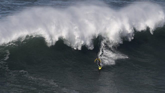Surfer Garrett McNamara of Hawaii riding a  wave Tuesday at Praia do Norte beach in Nazare, Portugal. He reportedly broke his own record by riding a wave Monday that was estimated at 100 feet tall.
