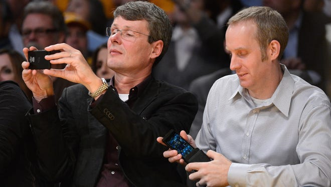 RIM CEO Thorsten Heins, left, takes a picture with a new BlackBerry device as Andrew Bocking, a senior vice president at RIM, puts his own  BlackBerry in a protective cover during a Los Angeles Lakers game in November.